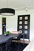 Charcoal dining table and basketwork shell chairs; collection of photos on black panel on wall