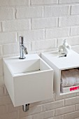 Cubic sink and shelf mounted on white brick wall