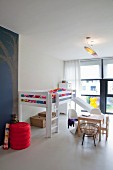 Loft bed with slide, child-size Panton chairs at small table and vintage trunks below bed in spacious child's bedroom