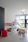 Geräumiges Kinderzimmer mit Bettrutsche, Kinder-Pantonstühlen am Kindertisch und Vintage Truhen unter dem Bett