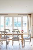 Ruhiges Esszimmer in klaren Naturfarben mit raumhoher Fensterfront, einem soliden Holztisch aus hellem Holz und weissen Vintage-Stühlen