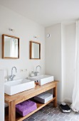 Bathroom with rustic washstand, twin square basins below two square, wood-framed mirrors