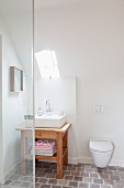 Wall-mounted toilet under sloping ceiling and small skylight above wooden washstand with rectangular basin
