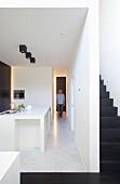 Long corridor between stairwell and kitchen in minimalist, open-plan interior