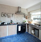 Masonry base units and modern cooker in simple kitchen with mottled blue floor tiles