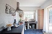 Einfache, gemauerte Küchenzeile mit Kochutensilien an Stange aufgehängt und Zinkeimer unter Natursteinspüle