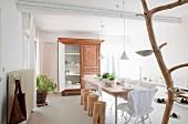 Gedeckter Tisch mit Baumstammhockern und Gartenstühlen mit Hussen; Kunstobjekt aus Baumstamm mit Porzellanschalen