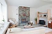 Wohnraum mit einfachen, hellen Möbeln und natursteinverkleidetem Kamin