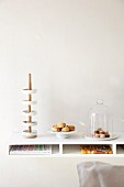 Modern cake stand made from dishes on wooden pole, small plate of pastries and glass cover