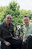 Men with dog posing on balcony