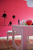 Black figures painted on pink wall behind white wooden table and bench