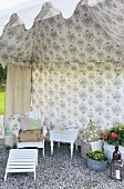 Vintage garden furniture in open-fronted tent with floral pattern on inside wall