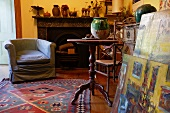 Corner of vintage-style living room - armchair with loose cover in front of open fireplace and wooden side table next to stack of paintings