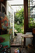 Stack of painting and vintage stool in studio with open glass door and view of garden