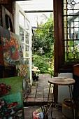 Bilderstapel und Vintage Hocker im Atelier mit offener Glastür und Blick in den Garten