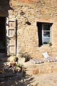 Cushions on stone bench below window on outside wall of Mediterranean stone house