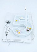 Floating daisies and lit birthday candle in white china dish in the shape of a number