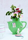 Posy of bellis and herbs in green retro jug