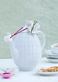 White, retro china coffee pot with fabric butterfly next to plate of biscuits