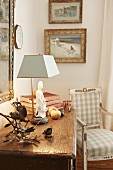 Collection of old ornaments on rustic chest of drawers next to antique country-house chair in corner