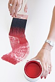 Hands of well-groomed woman wearing jewellery working with red paint and paintbrush
