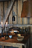 Candles and animal figurines on rustic table in wooden cabin