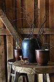 Kleine Rehfigur und Vasen mit Zweigen auf einem Holzhocker in einer Hütte