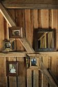 Fotos mit Holzrahmen an Wand und an Holzbalken in einer Hütte