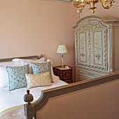 Patterned scatter cushions on antique sleigh bed and wardrobe painted with floral motifs in corner of bedroom