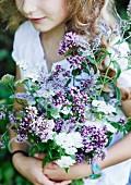 Girl holding bouquet of fragrant herbs in garden