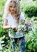 Blonde girl picking flowering herbs in garden