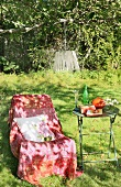 Throw on comfortable chair and garden table in shade of a tree