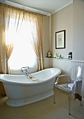 Freestanding bathtub in a traditional bathroom with modern plexiglass chair