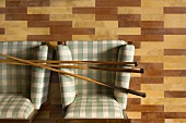 Three billiard cues lying across arms of two checked armchairs in room with multicoloured parquet floor