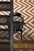 Antique spindle-back chair below metal staircase in room with parquet flooring in contrasting colours