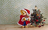 Teddy bear dressed as Father Christmas and toy ornaments next to Christmas tree