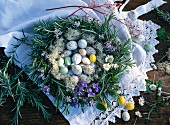 Easter eggs in a wreath of rosemary with violets and daisies