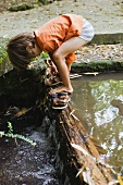Boy putting on sandals on tree trunk across stream
