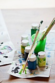 Various paints, paintbrushes and craft paper with paint tests