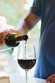 Man pouring glass of red wine