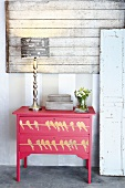Lamp with printed paper shade, box and vase of flowers on chest of drawers painted red with bird motif