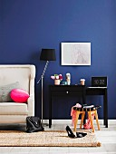 Black console table next to partially visible couch with white leather upholstery against royal blue wall