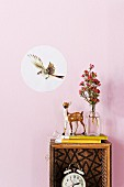 Decorative sticker with picture of flying bird and deer ornament on upcycled box shelf on wall painted pastel pink