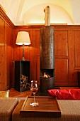 Antique-style table lamp next to modern, designer log burner made of unpolished steel in wood-panelled fireplace room of Schloss Schauenstein
