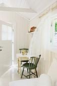 Frischer Wind bewegt die Chiffongardine in hellem, sommerlichem Raum mit geöffneter Tür