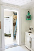 Foyer of summer cottage with pastel blue wooden steps and sun hat and handbag hanging on small coat rack