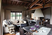 Light and dark natural palette: open living-dining room under an imposing wood beam ceiling