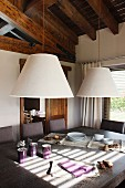 Two conical lampshades above a dining table and open wood beam ceiling