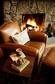 Cosy spot in front of fireplace - brown leather armchair, side table and open fire
