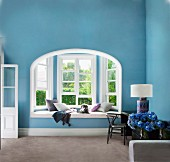 Blue, art nouveau living room with window seat and desk against wall